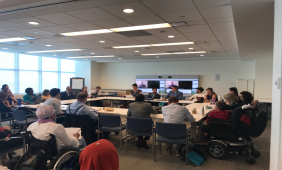 SGPWD official delegation meeting. International Sign interpretation and captioning displayed on the screen. Participants sitting around a large square table.