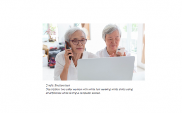 Two older women with white hair wearing white shirts using smartphones while facing a computer screen.