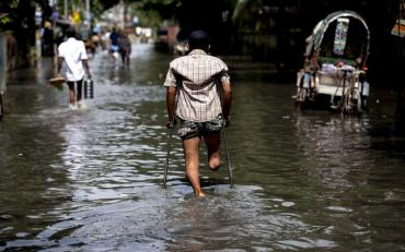 A person with disability using assistive technology in the middle of the flooded street.