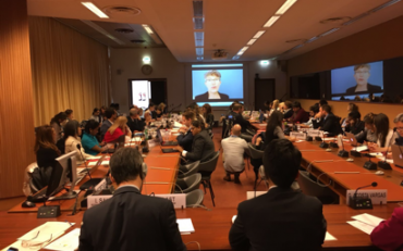 shows the room of the event, with a great level of concurrence, and Chair person of the CRPD Committee Theresia Degener`s video presentation on the back