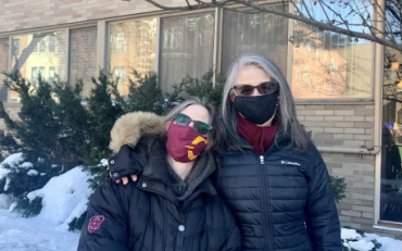 A women and her daughter wearing face masks.