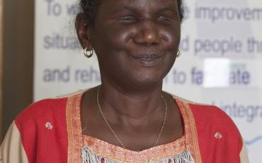 the photo of Ms Donatilla Kanimba, who is a blind person, wearing beautiful traditional dress in pink and orange colors.