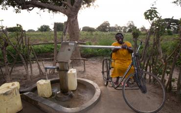 Publically available clean water being accessed by a person with a disability in Kenya