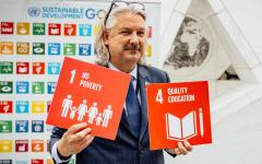 Colin Allen with SDG signs for Goal 1 No Poverty and Goal 4 Quality Education