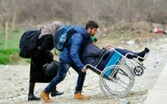 A man pushes a young boy in a wheelchair through a refugee camp