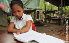 A young female student with amputated hands writes in her notebook.